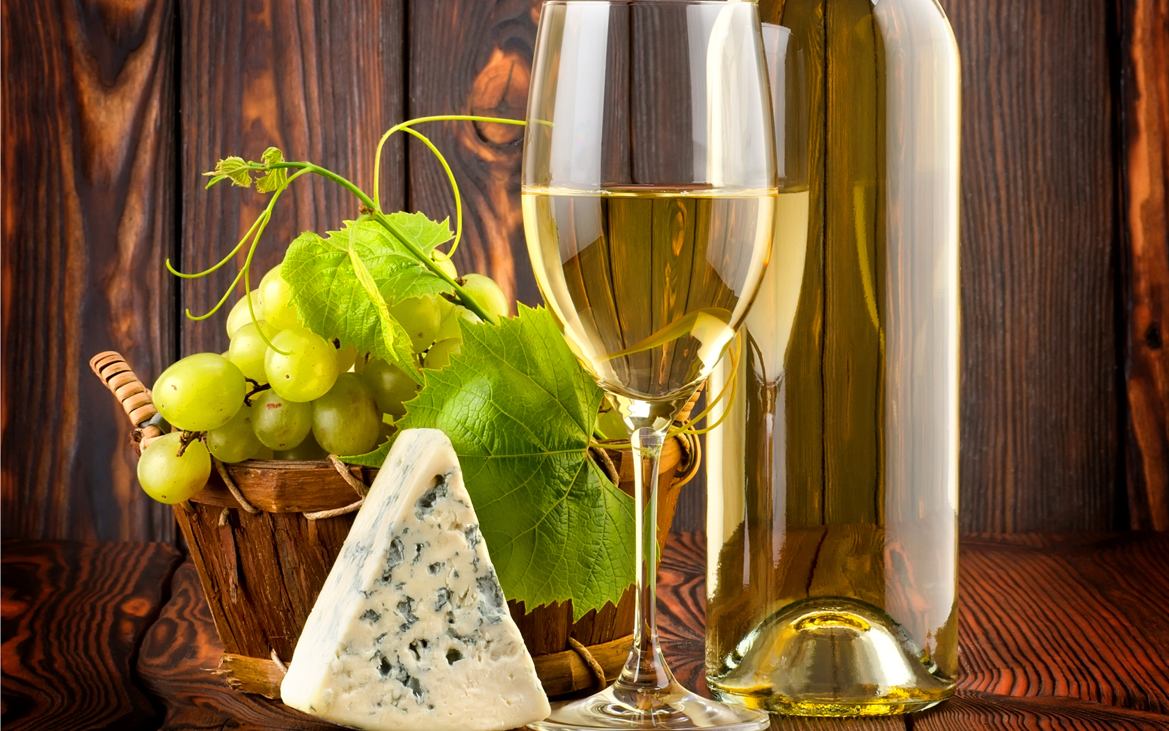 415495_stol_butylka_vino_beloe_bokal_loza_listya_vinograd_1680x1050_(www.GdeFon.ru)